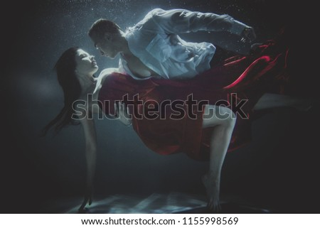 Couple swimming underwater with beautiful dress - Artistic dreamy portrait #1155998569