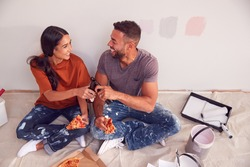 Couple Taking A Break And Drinking Beer And Eating Pizza As They Decorate Room In New Home Together