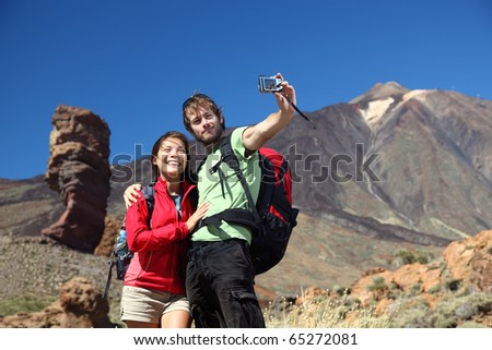 Couple taking picture having fun outdoors on vacation on Tenerife, Canary Islands. The volcano Teide and the famous Garcia Rock in the background. Young beautiful couple. - stock photo
