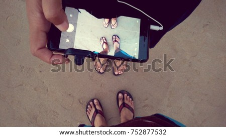 Couple taking picture of their feet on the Guhagar beach sand using mobile camera in India with retro / vintage filter effect