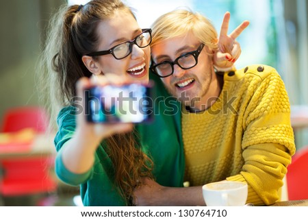 Couple taking self portrait, focus on camera