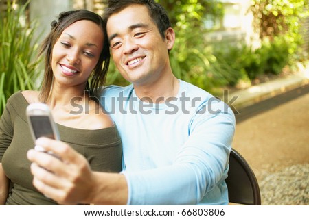 Couple taking self-portrait with cell phone - stock photo