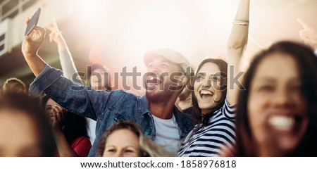 Couple taking selfie while cheering at stadium. Excited man and woman fans taking selfie while watching match in stadium.