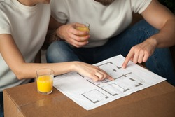 Couple talking about interior design with home plan, man and woman discuss renovation ideas pointing on blueprint holding orange juice, planning house remodeling apartment furnishing, close up view