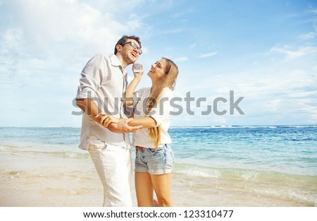 couple talking by phone on beach