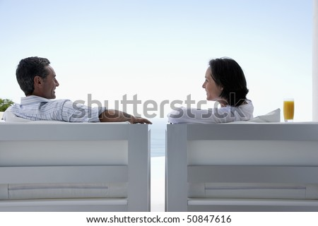 Couple talking, sitting on lounge chairs, outdoors