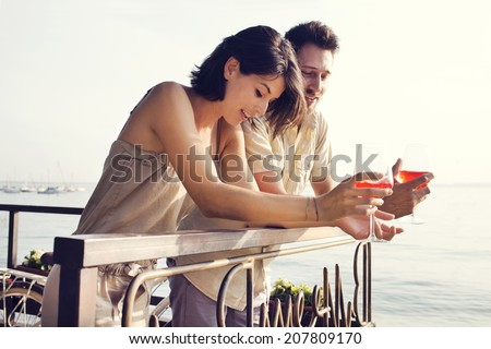 Couple talking while having spritz in a lake view terrace