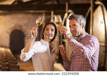 Couple tasting a glass of white wine in a traditional cellar surrounded by wooden barrels.