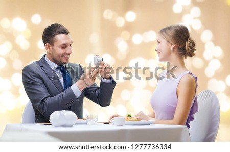 couple, technology and leisure concept - smiling man taking picture of wife or girlfriend by digital camera at restaurant over festive lights on beige background