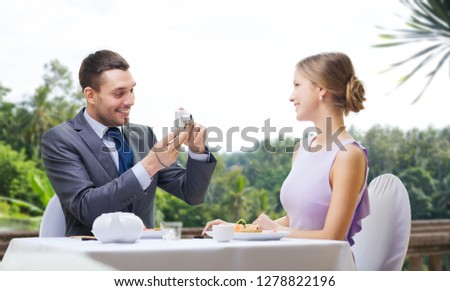 couple, technology and leisure concept - smiling man taking picture of wife or girlfriend by digital camera at restaurant over summer background
