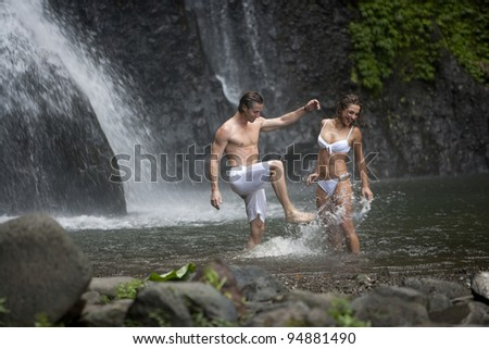 Couple throwing water at each other under waterfalls.