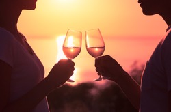 Couple toasting wine glasses in romantic date setting.