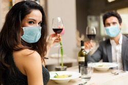 Couple toasting wineglasses in a luxury restaurant and wearing masks, coronavirus concept