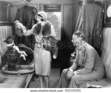 Couple together in a train and feeding a dog