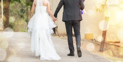 Couple together walking and hold hand before wedding day. lady in wedding dress walk with her husband, out door pre wedding activity, marriage and wedding concept