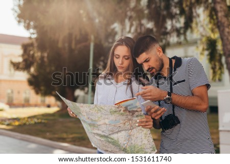 couple tourist in sightseeing in city using paper map and smartphone