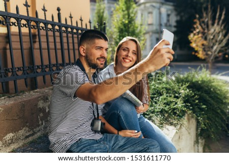 couple tourist in sightseeing in city using paper map and taking picture mobile phone