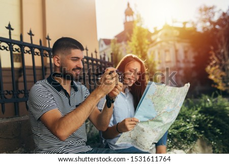 couple tourist in sightseeing in city using paper map and taking picture with camera