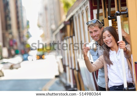 Couple tourists riding the popular touristic attraction cable car system in San Francisco city, California during summer travel holidays. People having fun taking selfie picture and tourist photos. #514980364
