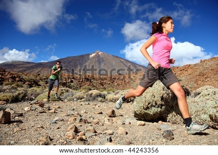 Couple trail running in spectacular volcano landscape on Teide, Tenerife.