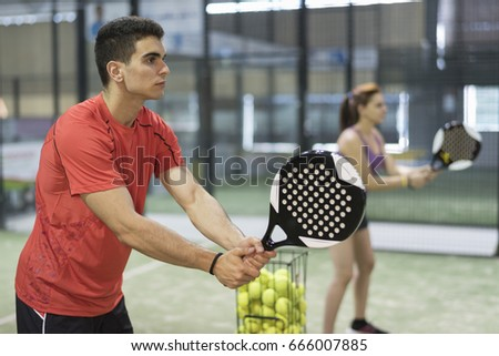 Couple training paddle tennis in court with racket and balls in recreation activity