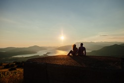 couple travel mountains at sunset. Picturesque landscape. Travelling Europe at honeymoon. Mountains and sea view at sunset.