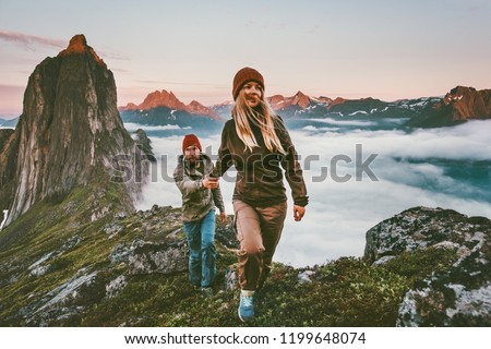 Couple travelers holding hands hiking together in Norway travel healthy lifestyle concept active vacations outdoor Segla mountain sunset landscape