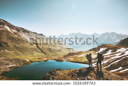 Couple travelers holding hands on mountain cliff over lake together love and Travel Lifestyle wanderlust concept adventure vacations outdoor aerial view  #1026189763