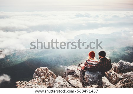 Couple travelers Man and Woman sitting on cliff relaxing mountains and clouds aerial view  Love and Travel happy emotions Lifestyle concept. Young family traveling active adventure vacations #568491457