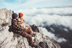 Couple travelers Man and Woman sitting on rocks relaxing mountains and clouds landscape Love and Travel happy emotions Lifestyle concept. Young family traveling active adventure vacations