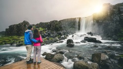 Couple travelers travel to Oxararfoss waterfall in Thingvellir National Park, Iceland. Oxararfoss waterfall is famous waterfall attracting tourist to visit Thingvellir.