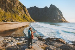 Couple traveling together summer vacations family outdoor lifestyle romantic honeymoon relationship man and woman enjoying Kvalvika beach sea and rocks landscape in Norway