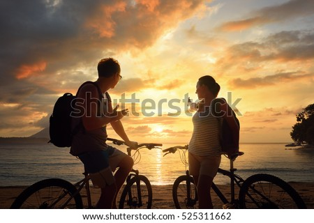 Couple travellers with bicycles watching sunset. Summer nature background with beautiful Sky and Sea. Active leisure concept.