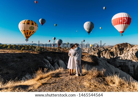 Couple travels the world. Honeymoon trip. Married couple on vacation. Tourists in Cappadocia. Man and woman resting in Turkey. Flying balloons at sunrise. World tour. Man and woman among balloons Foto stock ©
