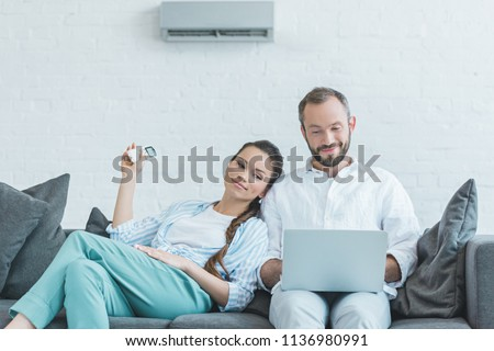 couple turning on air conditioner during the summer heat while using laptop #1136980991