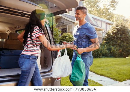 Couple Unloading Shopping Bags From Car