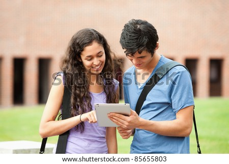 Couple using a tablet computer outside a building