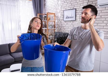 Couple Using Bucket For Collecting Water Leakage From Ceiling And Calling Plumber On Cellphone Foto stock ©