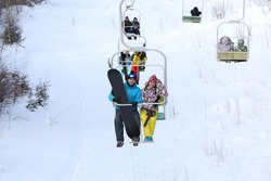 Couple using chairlift at mountain ski resort. Winter vacation