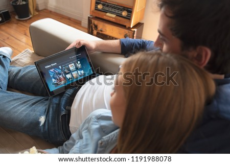 Photo of  Couple using digital tablet for watching movie on VOD service. Video On Demand television internet stream multimedia concept