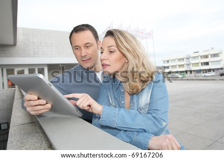 Couple using electronic tab in the street