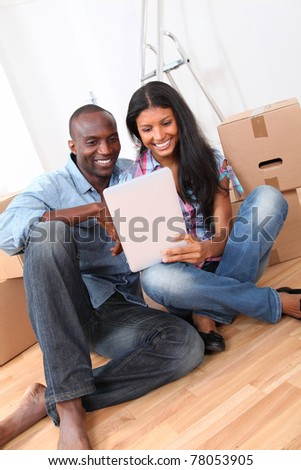 Couple using electronic tablet in their new house