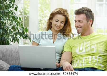 Couple using laptop computer at home together, looking at screen, smiling.