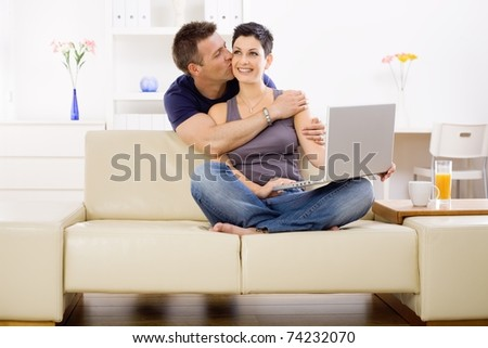 Couple using laptop computer at home together, man hugging and kissing woman, smiling.?