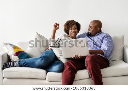 Couple using laptop together on the couch