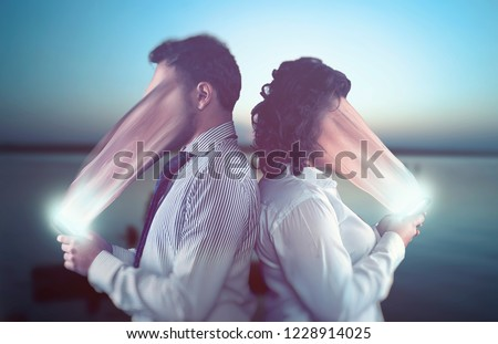 Couple using smartphones on a date.The concept of phone addiction. Face absorbed by the phone.