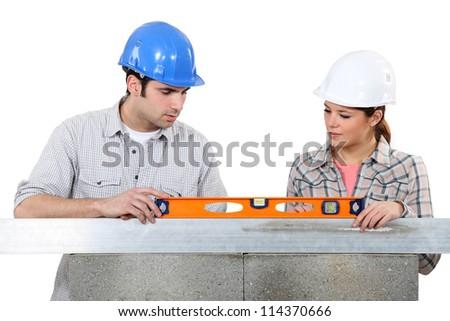 Couple using spirit-level on wall