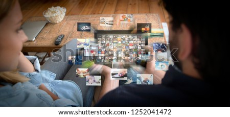 Couple using tablet for watching VOD service. Video On Demand television with abstract flying images