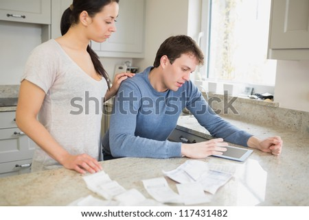 Couple using tablet pc to calculate finances in kitchen