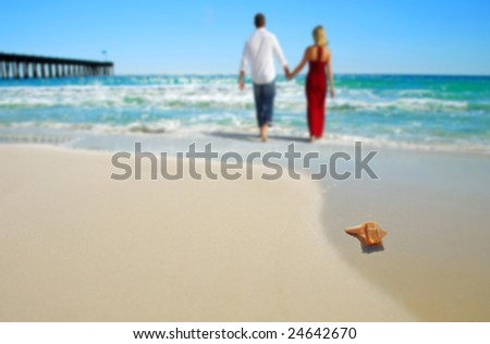 Couple wading in surf at beach by shell